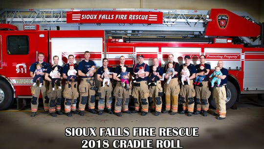 """Twelve Sioux Falls firefighters pose for the first ever """"cradle roll"""" for Sioux Falls Fire Rescue. Fourteen babies were added to the SFFR family in 2018."""