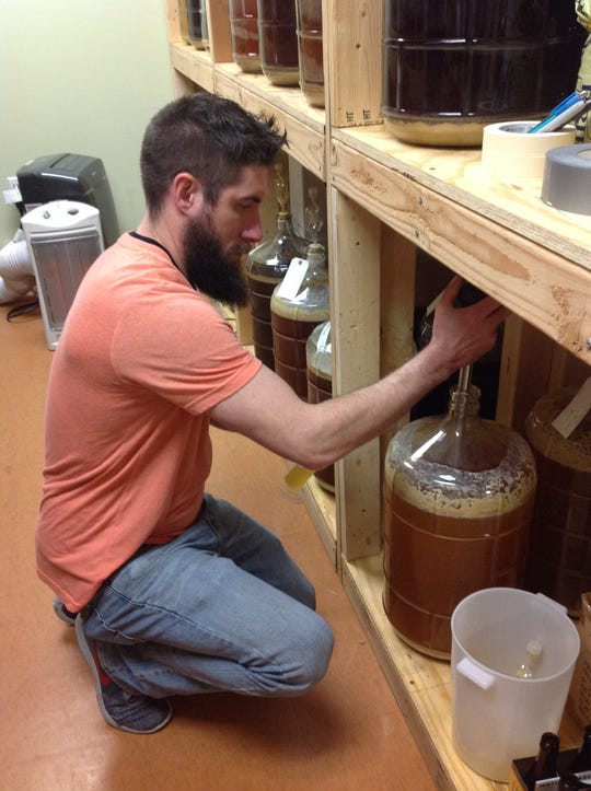 Show Me Brewing employee John Gilbey samples a beer.