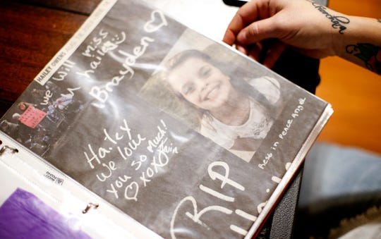 Chandra Calhoun, the aunt of Hailey Owens, flips through a book with photos of Hailey and newspaper clippings from the case on Thursday, Jan. 17, 2019.