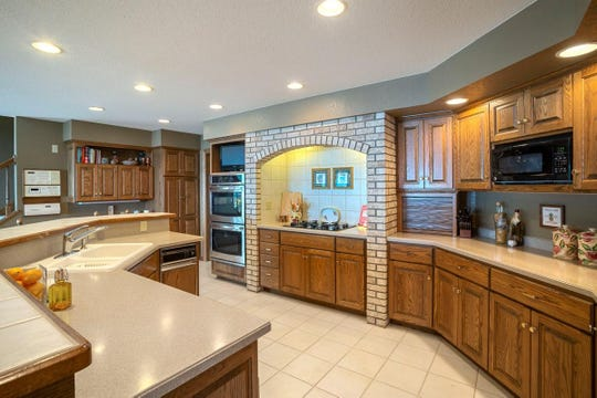 The kitchen boasts many elegant touches – such as Corian countertops, a brick archway over the cooktop and a spacious ceramic eating counter.
