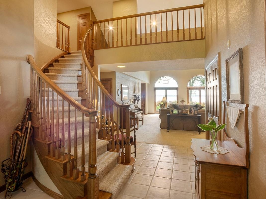 The upper floor sits atop a curling banisterstaircase from the foyer.