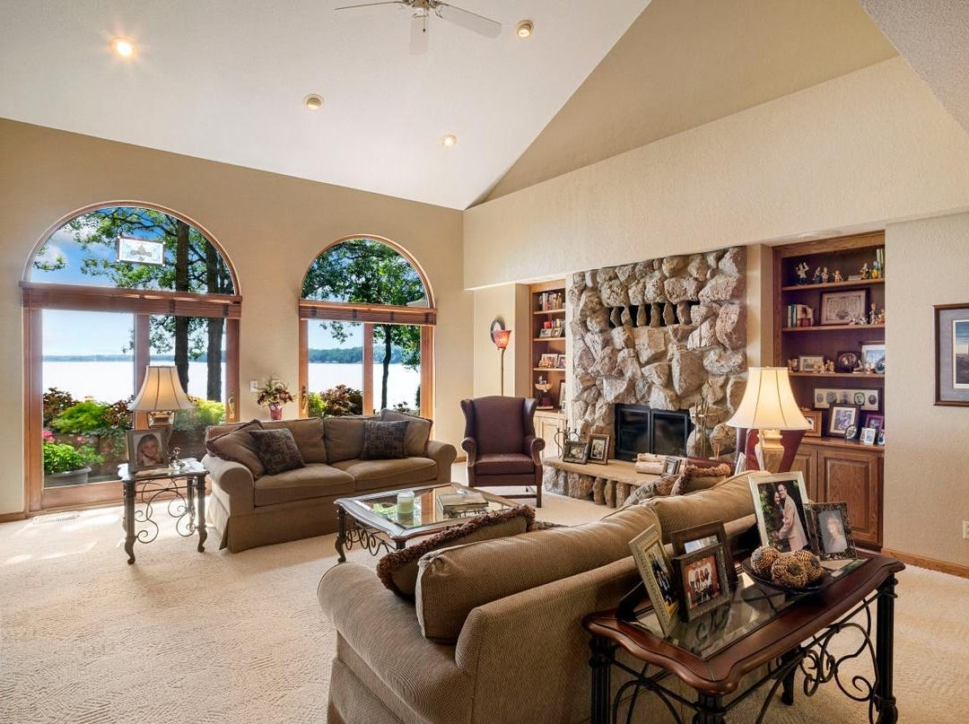 The great room is a full two stories high with a wall of arched windows that affords a breathtaking view of the lake.