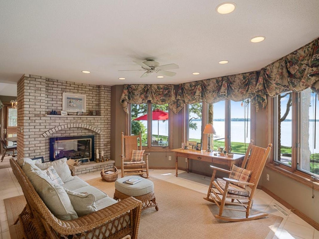 An informal dining room and a cozy sitting area flank the two-sided brick kitchen fireplace.