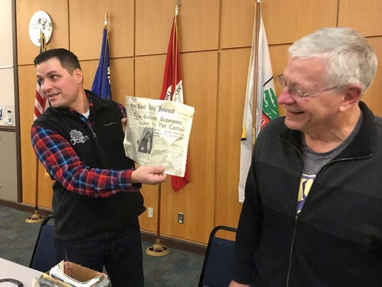 Jeff Rice, co-owner of Origin Family Homebuilders, and Tim Siebert, president of the Portage County Historical Society, open a time capsule formerly embedded in the wall of the old Grant School and presents the contents during a ceremony on Jan. 16 at the Portage County Library.