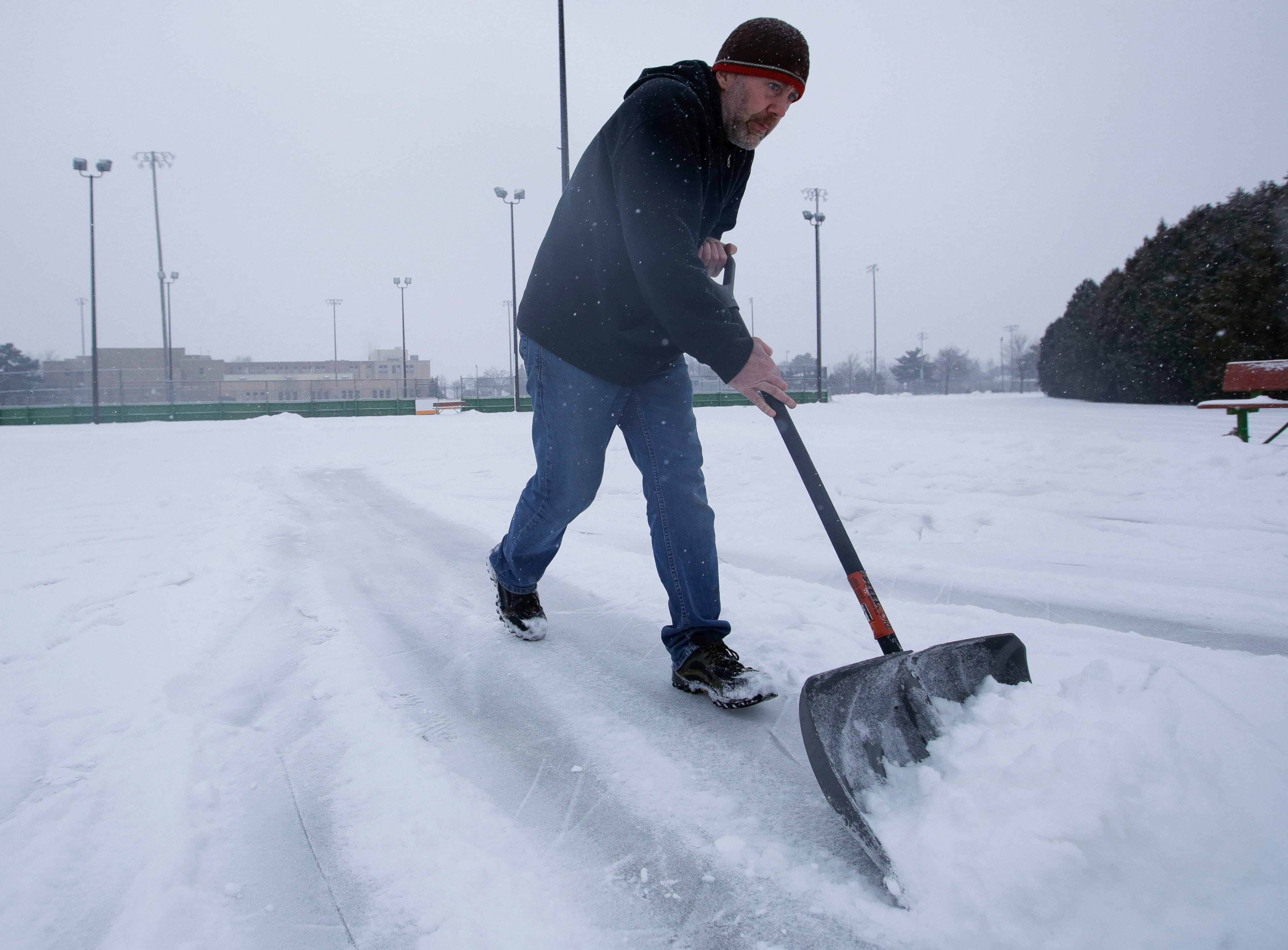 Paul Rath shovels snow off of the ice on Tuesday, January 22, 2019, at Goerke Park in Stevens Point, Wis. A snow storm rolled through the area on Tuesday and is expected to drop 6-8 inches of snow.Tork Mason/USA TODAY NETWORK-Wisconsin