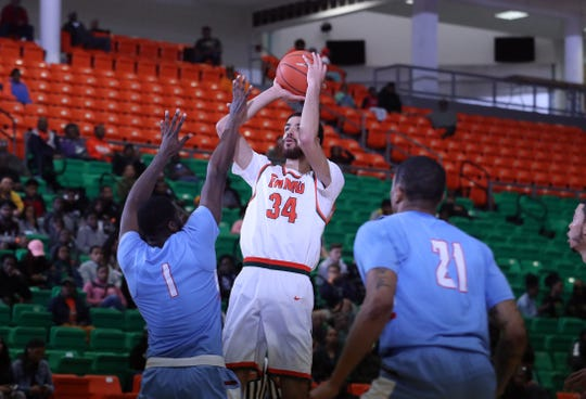 FAMU center Isaiah Martin pulls up for a jumper over Delaware State's D'Marco Baucum.