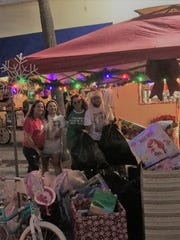 Event organizers Deb Pizzimenti, Suncoast CEO Deb Engle, Christa Stone and Jose Ruiz with toys donated at LeGit's Downtown Toy Drive Block Party in Fort Pierce.