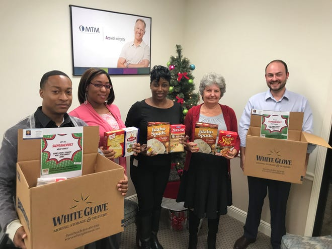 MTM Transit employees hold some of their collection of food for the White Glove Moving Holiday Food Drive.