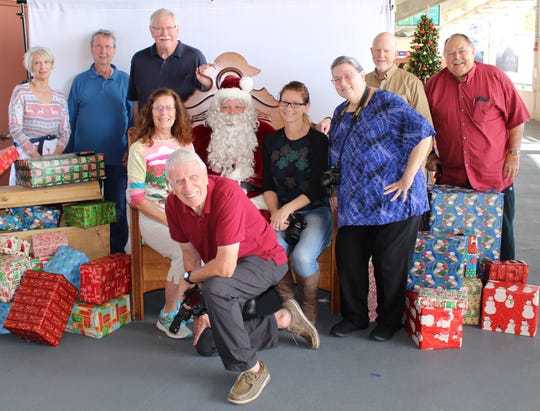 Members of the Treasure Coast Photography Center volunteered to take photos of area youth at the third annual Breakfast with Santa. Pictured, from left, Kathryn Turney, James Brown, John Furlong, Ginger Shoun, Michael Adkins, and Robbie Sheets; seated, Shawn Dufault, Santa and Crystal Speirs, with Jeff Kraengel, kneeling.