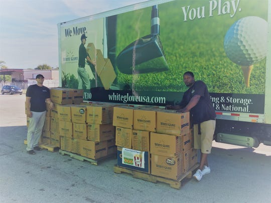 David Menillo and Ollice Ervin of White Glove deliver food collected during the 2018 White Glove Moving Holiday Food Drive. More than 2,800 pounds of food was collected and delivered to the Treasure Coast Food Bank.
