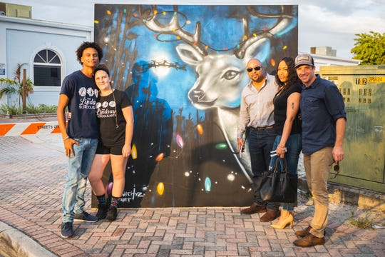 Artist Louichyz and Dorian Bridge with Lindsay's School of Art, along with volunteers, pose by the reindeer art created during LeGit's Downtown Toy Drive Block Party and donated to Club PURE.