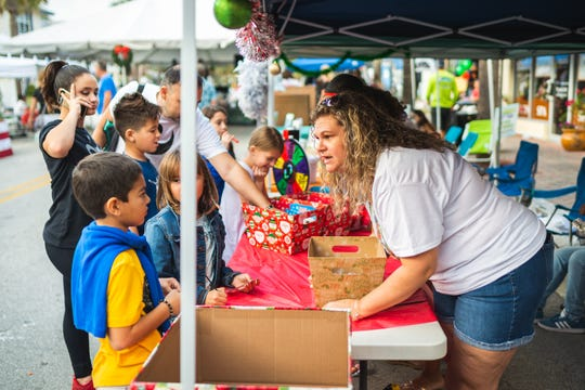 Tricia Cote, right, lead case manager at Suncoast Mental Health Center, shares crafts with children attending LeGit's Downtown Toy Drive Block Party in Fort Pierce.