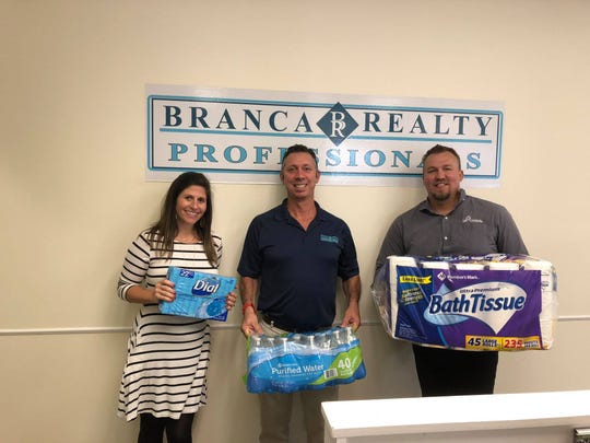 Branca Real Estate Professionals showcase some of the donations received for the White Glove Moving Holiday Food Drive.