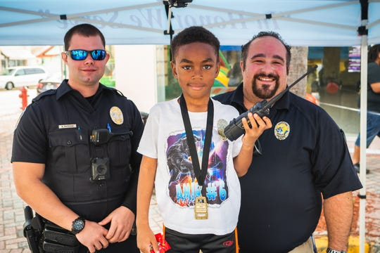 Fort Pierce Police Department volunteers talk to this young man at LeGit's Downtown Toy Drive Block Party in Fort Pierce.