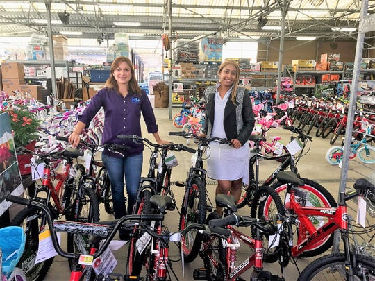 Nixalys Vega, left, division director of Children and Outpatient Services, and Maggie Wynter, Wraparound Team leader, buy 10 bicycles for children in need associated with New Horizons of the Treasure Coast.