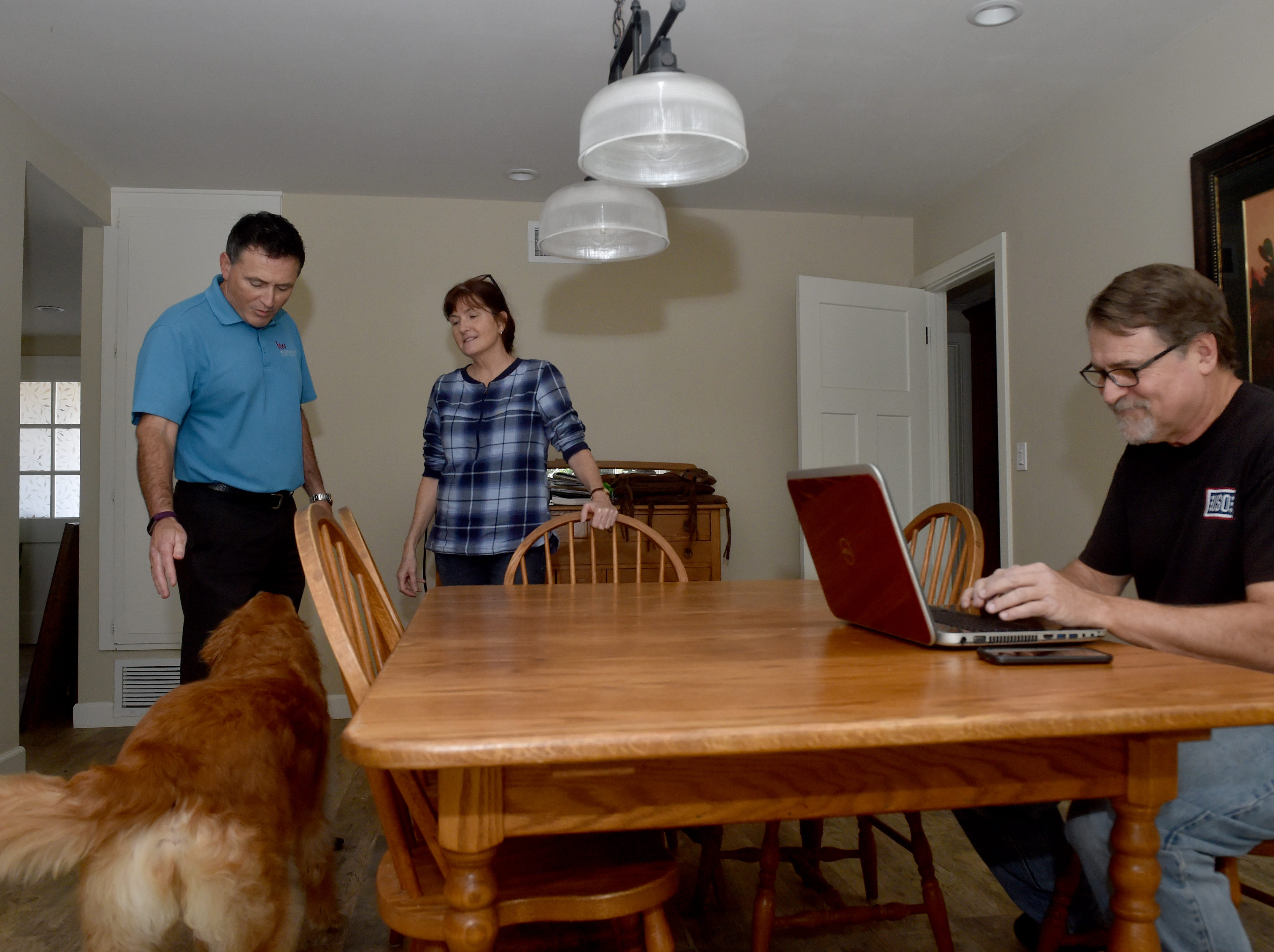 Jeff Landau, a Simi Valley real estate agent, speaks with clients Kevin and Barbara Siminski as he is greeted by the family dog Molly in their Thousand Oaks home.