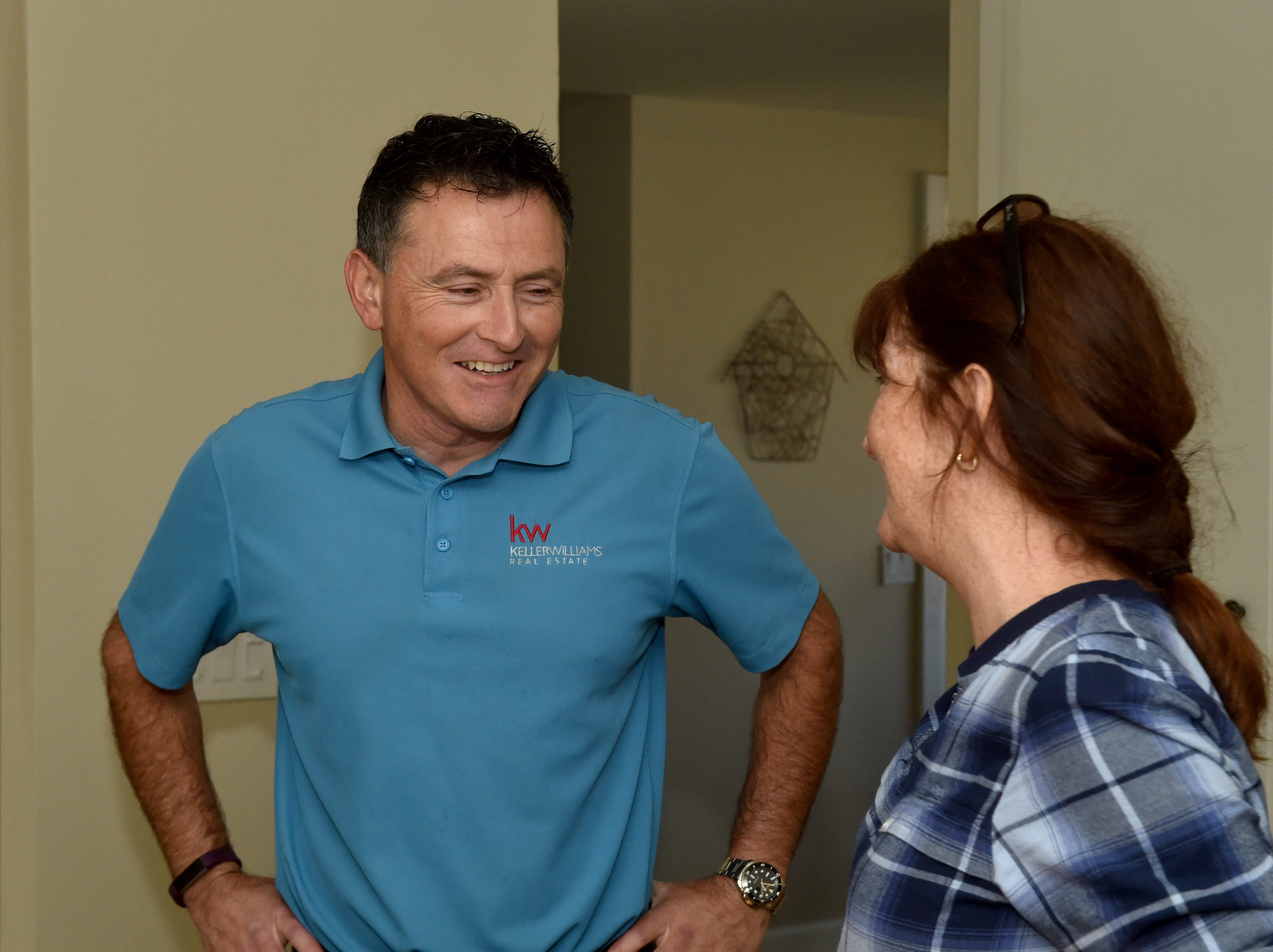 Jeff Landau, a local real estate agent working to stand out from his competitors, speaks with client Barbara Siminski at her home in Thousand Oaks.