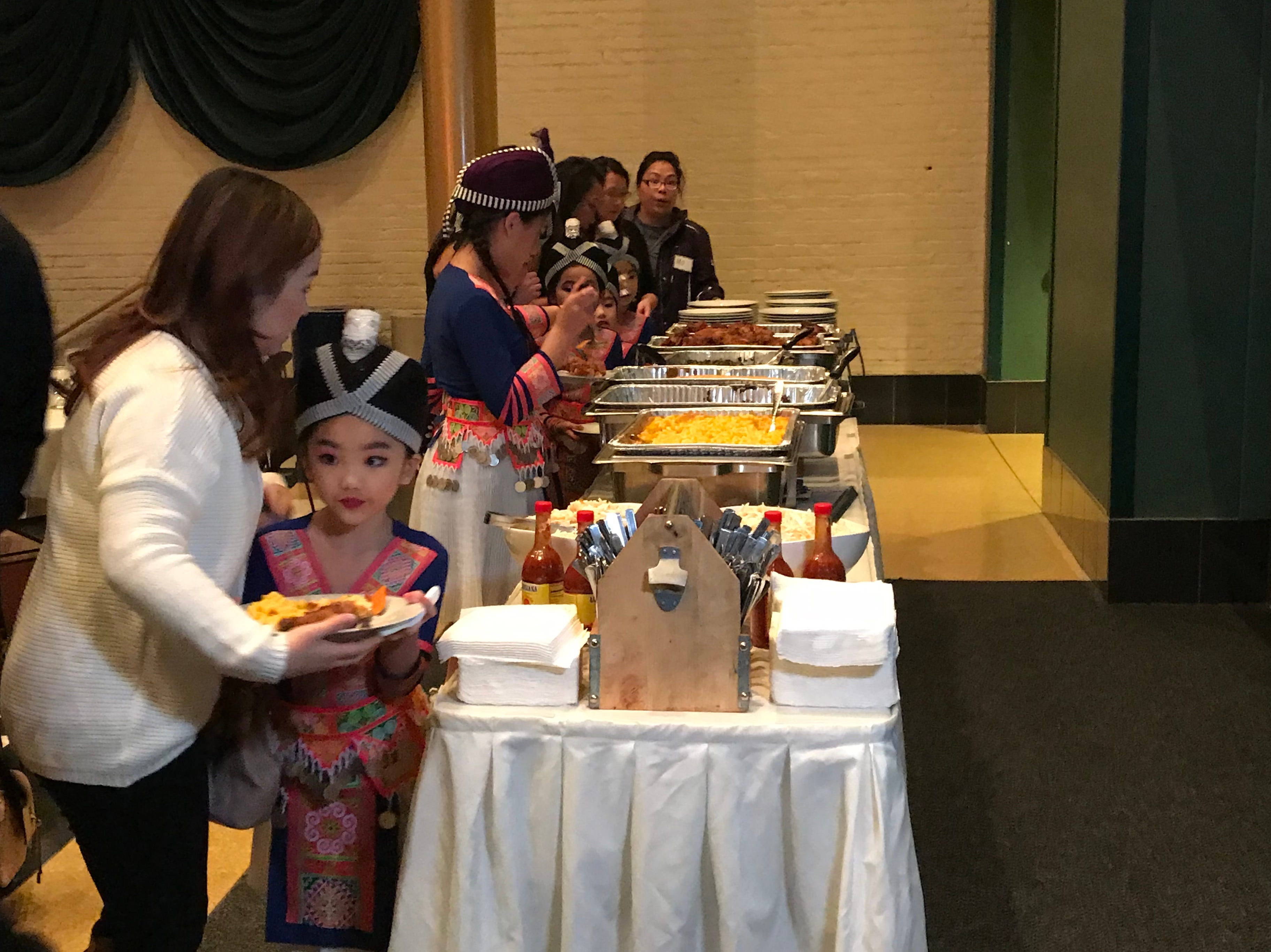 Girls from a Hmong dance group get dinner at the MLK Day celebration at the Grand Theater in Wausau.