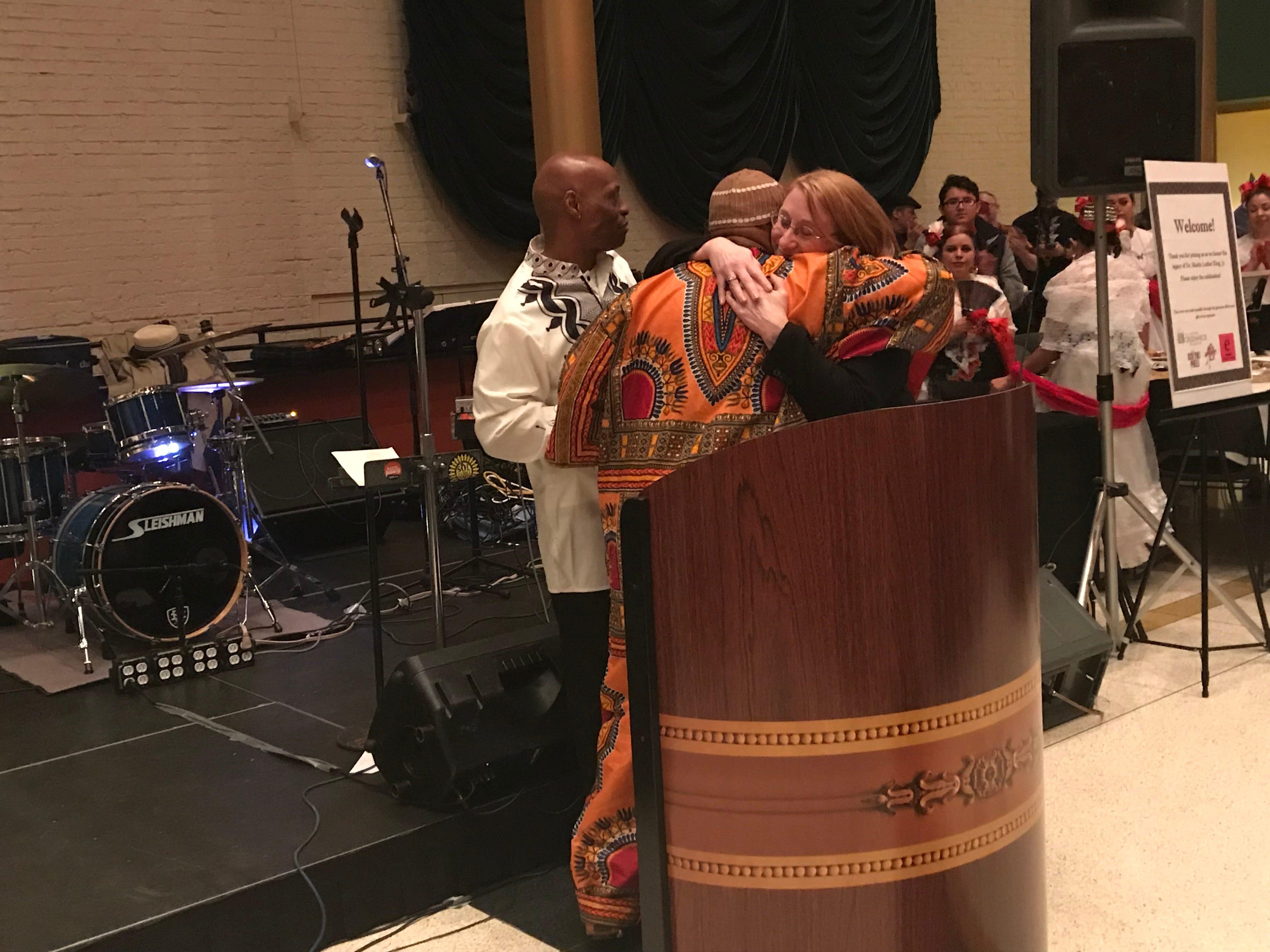 David Stuart hugs social justice award winner Kate Hephner at the MLK Day celebration at the Grand Theater in Wausau.