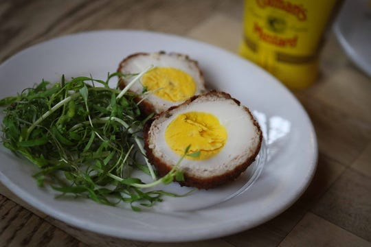 The Scotch Egg, a hard-cooked egg wrapped in house-ground local pork, lightly breaded and fried, is served with Coleman's mustard.