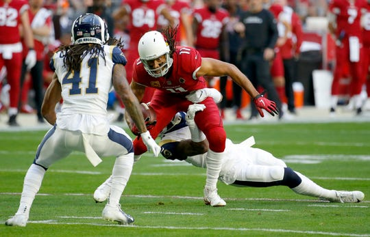 Arizona Cardinals wide receiver Larry Fitzgerald (11) is tackled by Los Angeles Rams strong safety John Johnson as defensive back Marqui Christian (41) looks on during the first half of an NFL football game, Sunday, Dec. 23, 2018, in Glendale, Ariz.