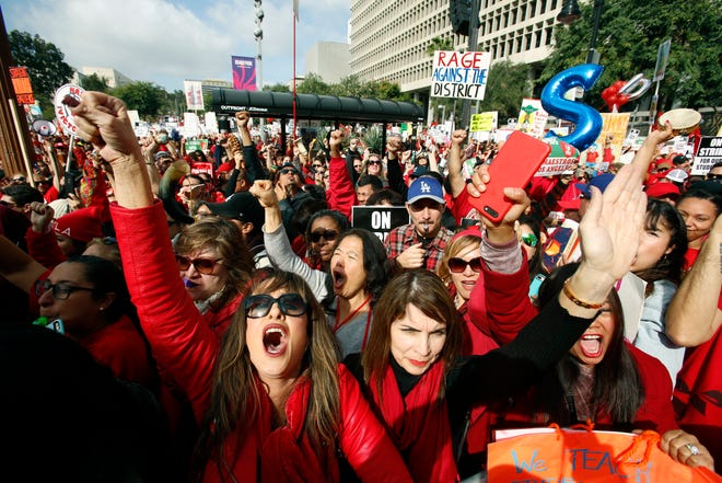 Educators rally as a strike against the Los Angeles Unified School District entered its fifth day outside City Hall in Los Angeles Friday, Jan. 18, 2019. Clashes over pay, class sizes and support-staff levels in the district led to its first strike in 30 years and prompted the staffing of classrooms with substitute teachers and administrators. (AP Photo/Damian Dovarganes)