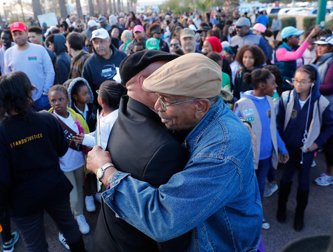 Rev. Gerald Richard II, left, greets Gene Blue before a march honoring Dr. Martin Luther King in downtown Phoenix.