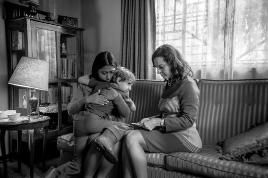 "Cleo (Yalitza Aparicio, left) comforts Pepe (Marco Graf) and Sofia (Marina de Tavira) after learning devastating news in ""Roma."""