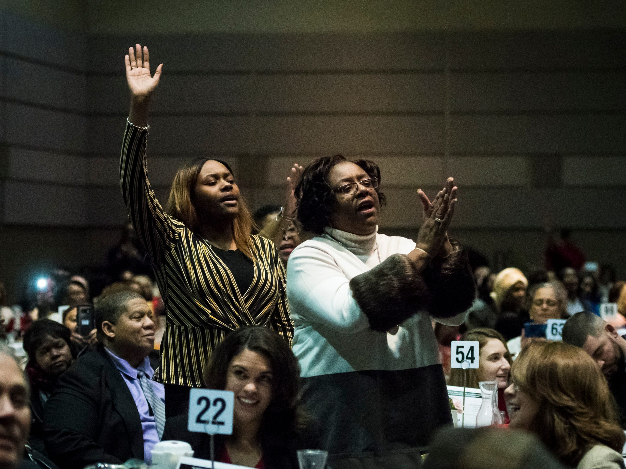 Attendees of the 34th Annual MLK Holiday Luncheon Celebration reacts to Pastor Donnie McClurkin, Jr. of Perfecting Faith Church in Freeport, N.Y., as he sings at The Lansing Center in downtown Lansing, Mich.