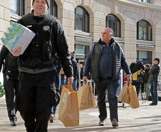 Chef Jose Andres, right, helps carry free meals to members of the U.S. Park Police outside his World Central Kitchen on Jan. 22.