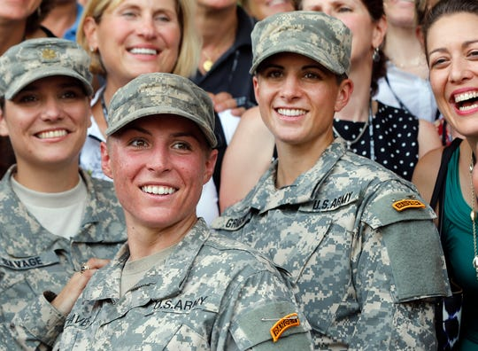 In this Aug. 21, 2015, file photo, Army 1st Lt. Shaye Haver, center, and Capt. Kristen Griest, right, pose for photos with other female West Point alumni after an Army Ranger school graduation ceremony at Fort Benning, Ga.