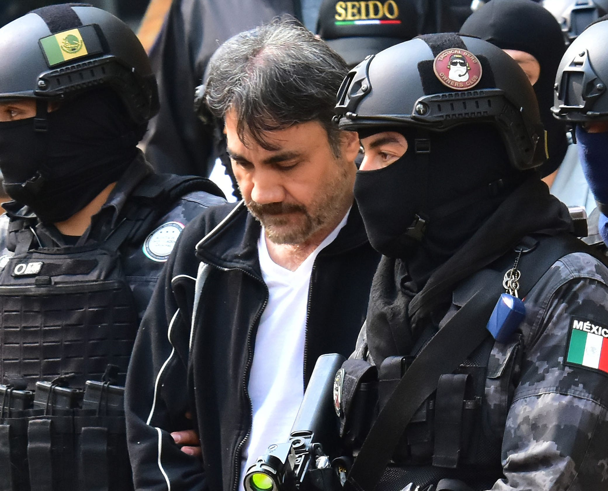 """Agents of the Criminal Investigation Agency and soldiers of the Mexican army escort senior lieutenant of US jailed drug lord, Joaquin """"Chapo"""" Guzman, Damaso Lopez (C) after arresting him, in Mexico City on May 2, 2017.   Mexico announced the arrest of a senior lieutenant of the jailed Joaquin """"Chapo"""" Guzman who was allegedly engaged in a bloody struggle to lead the Sinaloa crime syndicate."""