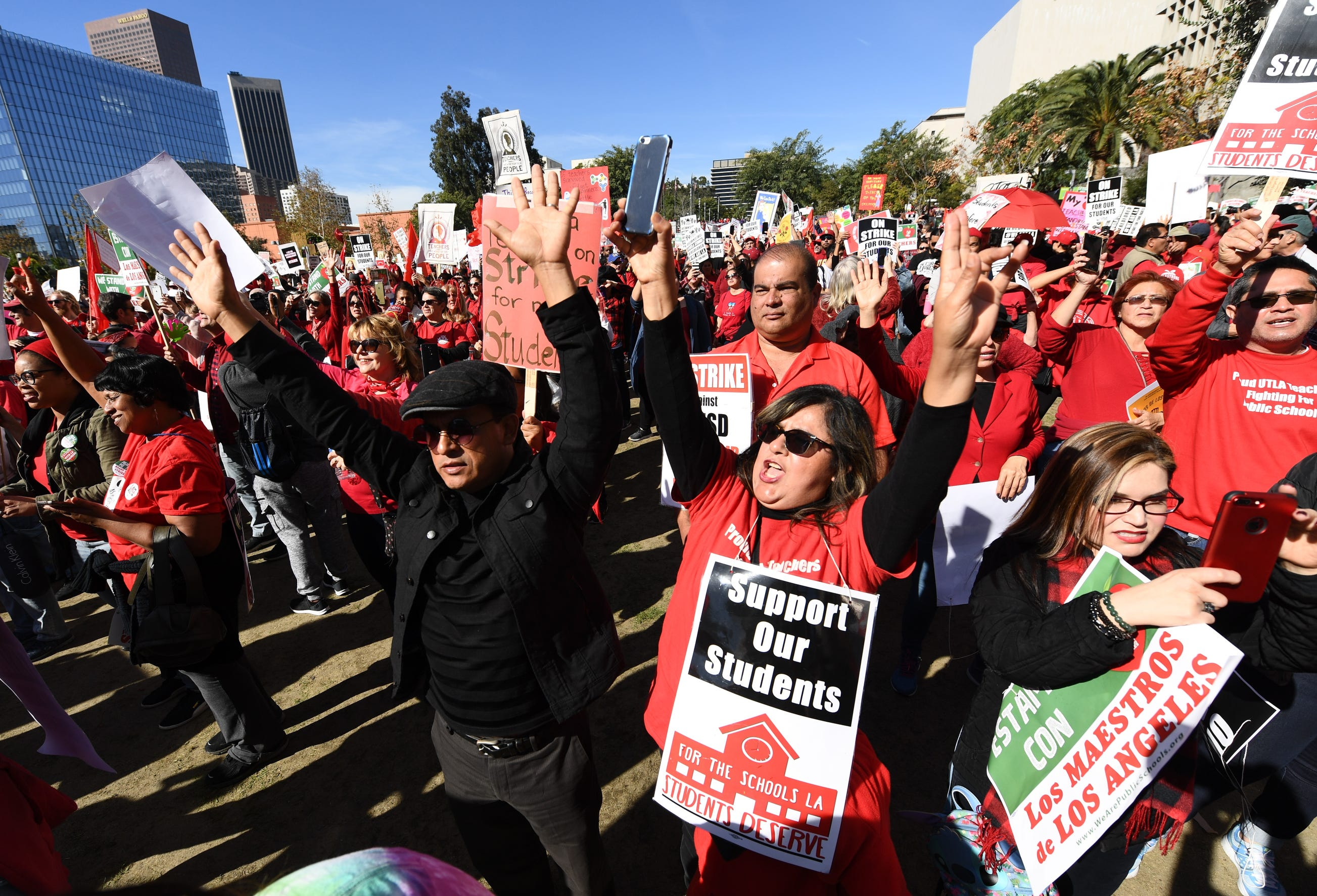 Striking L.A. teachers raise their arms as they hear the details on a new labor contract during a Jan. 22 rally in Grand Park in downtown Los Angeles.