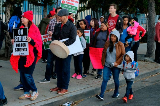 Parents arrive with their children to Evelyn Thurman Gratts Elementary School as people rally in support of Los Angeles school teachers,  Jan. 22, 2019, in Los Angeles.