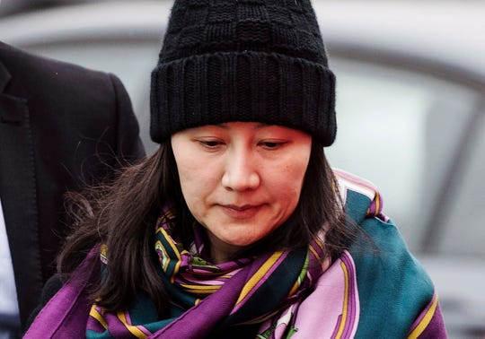 In this Dec. 12, 2018, file photo, Huawei chief financial officer Meng Wanzhou arrives at a parole office with a security guard in Vancouver, British Columbia. China on Tuesday, Jan. 22, 2019, demanded the U.S. drop a request that Canada extradite the top executive of the tech giant Huawei, shifting blame to Washington in a case that has severely damaged Beijing's relations with Ottawa.