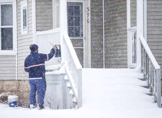 Fond du Lac mailman Tyler Donahue delivers mail Wednesday, January 23, 2019 in Fond du Lac, Wisconsin during a snowstorm. More than 6 inches of snow had fallen by 7 a.m. in the Fond du Lac area with heavy snow still falling.