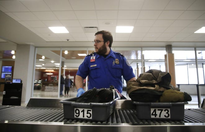 Nikolas Gray, a TSA officer working at the Appleton International Airport, moves a passenger's items through the checkpoint Tuesday, Jan. 22, 2019, in Appleton, Wis.