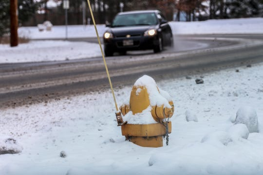 A yellow fire hydrant seems to be half covered with snow on a sidewalk alongside Ross Avenue after a snowstorm Wednesday, Jan. 23, 2019, in Weston.