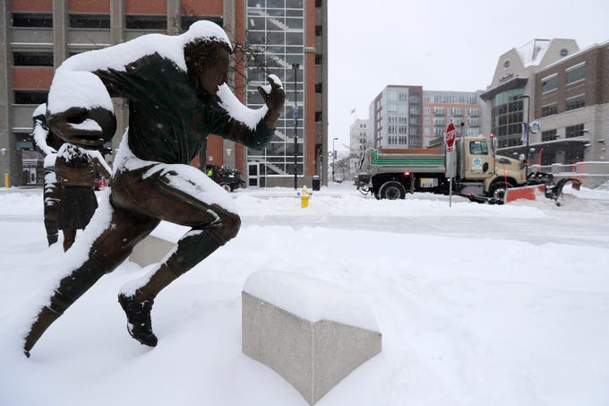 A snow plow clears the downtown streets by the statues on the Packers Heritage Trail during a snow storm on Wednesday, January 23, 2019 in Green Bay, Wis.