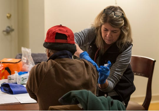 Leanora Chojnowski, R.N. of Visiting Nurse Association, gives a shot to a man in need. New Jersey housing advocates conduct the state's annual NJCounts, a point-in-time count of homelessness.       