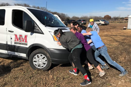 McMurry University students on a mission trip to the Dallas area faced some challenges, such as pushing their van out of the mud.