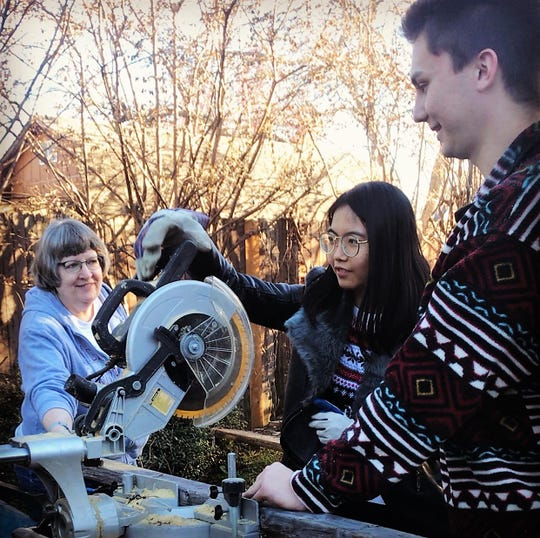 Yuwei Bao, a McMurry University student from China, learns how to handle a saw during a mission trip. At left is McMurry Chaplain Marty CashBurless. At right is McMurry student Colin Craft.