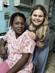 ACU's Sabrina Zeiler takes a break with caregiver at a hospital in Haiti.