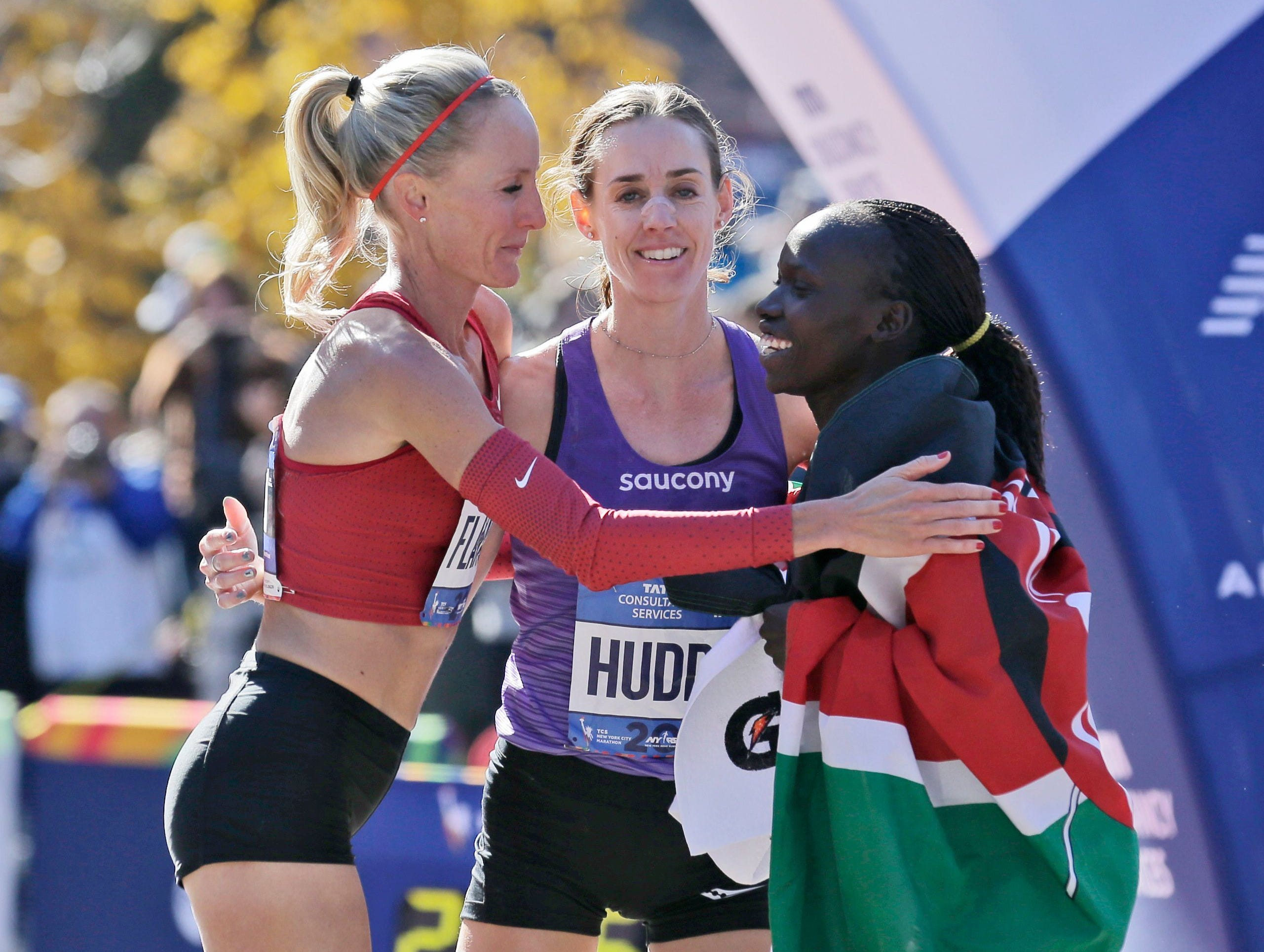 First-place finisher Mary Keitany of Kenya, right, greets American runners Shalane Flanagan, left, and Molly Huddle at the finish line of the New York City Marathon in New York, Sunday, Nov. 4, 2018. Huddle is a native of Elmira, NY.