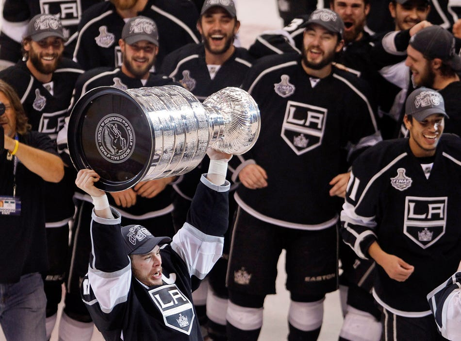 Los Angeles Kings captain Dustin Brown, a native of Ithaca, holds up the Stanley Cup after the Kings beat the New Jersey Devils 6-1 during Game 6 of the NHL hockey Stanley Cup finals, Monday, June 11, 2012, in Los Angeles.