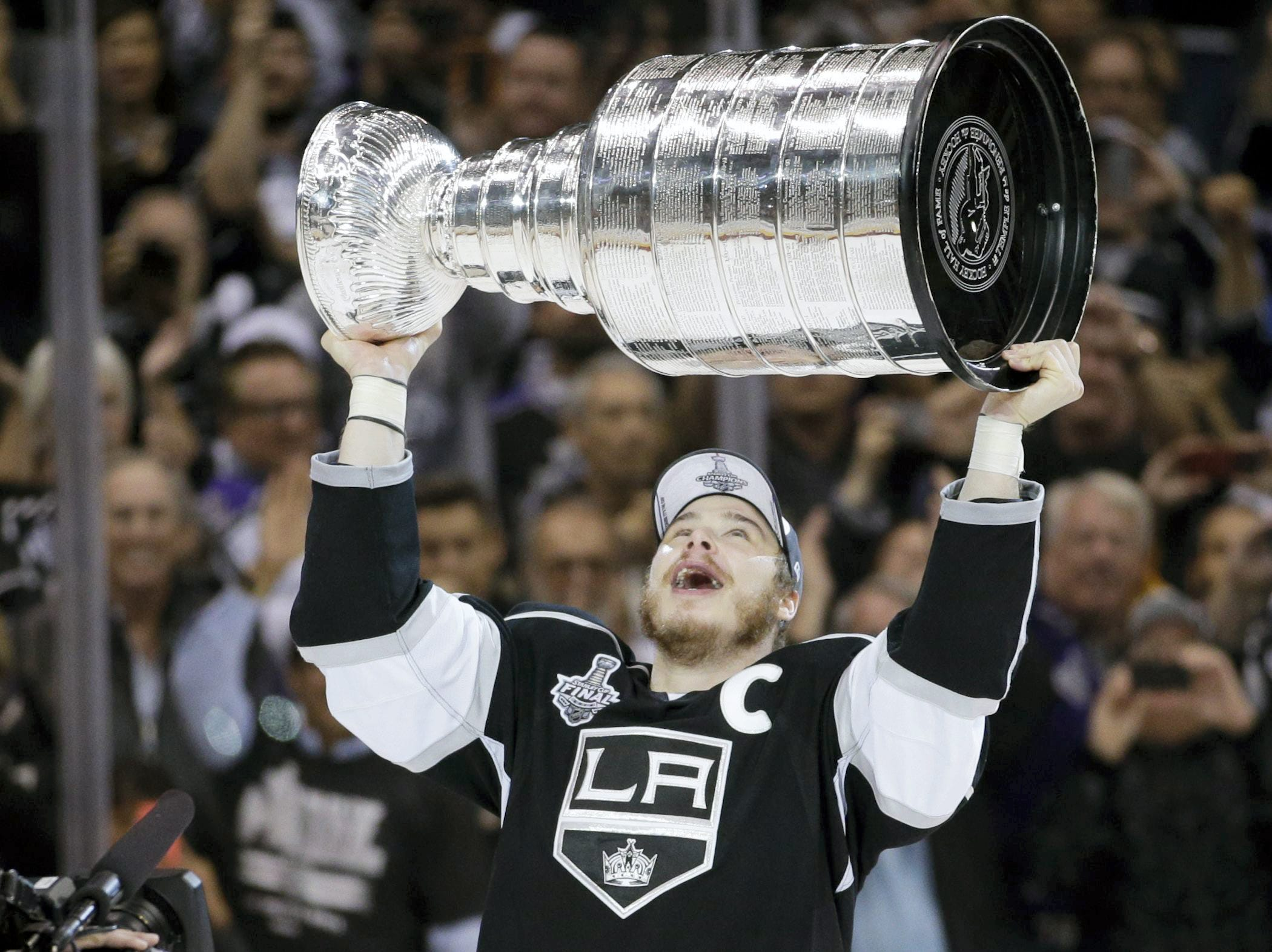 Los Angeles Kings right wing Dustin Brown, an Ithaca native, raises the Stanley Cup after beating the New York Rangers in overtime in Game 5 of the NHL Stanley Cup Final series Friday, June 13, 2014, in Los Angeles.
