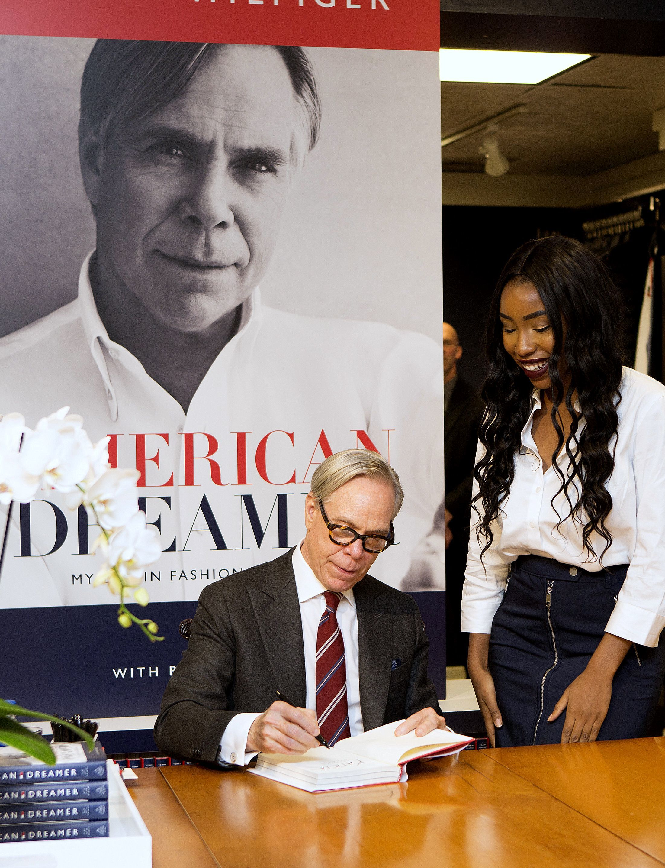 """Fashion designer and Elmira native Tommy Hilfiger signs a copy of his new book, """"American Dreamer: My Life in Fashion & Business,"""" for a fan at the Hilfiger store in Corning."""