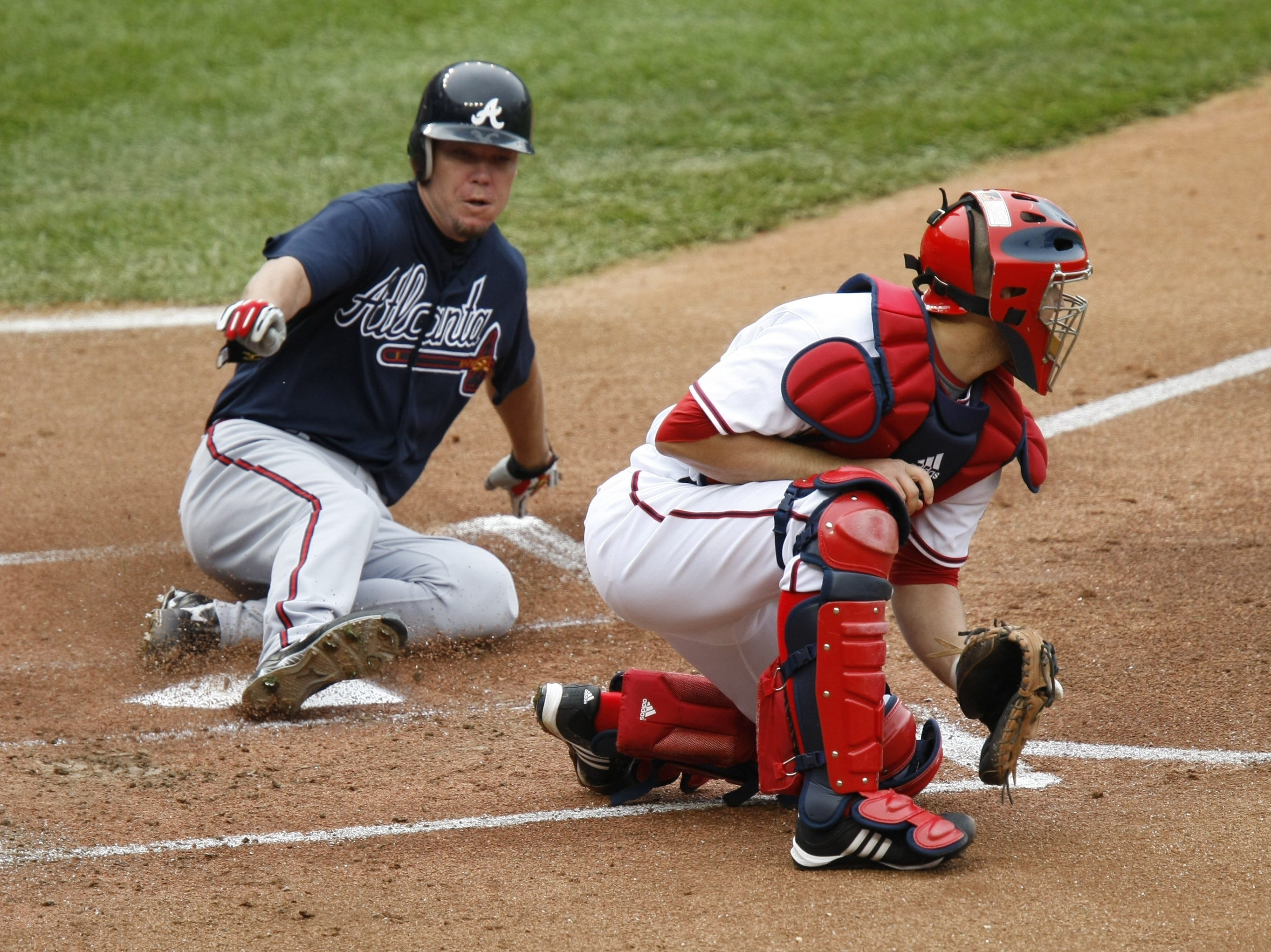 Atlanta Braves' Chipper Jones, left, slides safely into home plate on a two-run single by Atlanta Braves' Yunel Escobar as Washington Nationals catcher Josh Bard, right, waits for the ball during the first inning of a baseball game, Saturday, Sept. 26, 2009, in Washington. Bard is a native of Ithaca, NY.