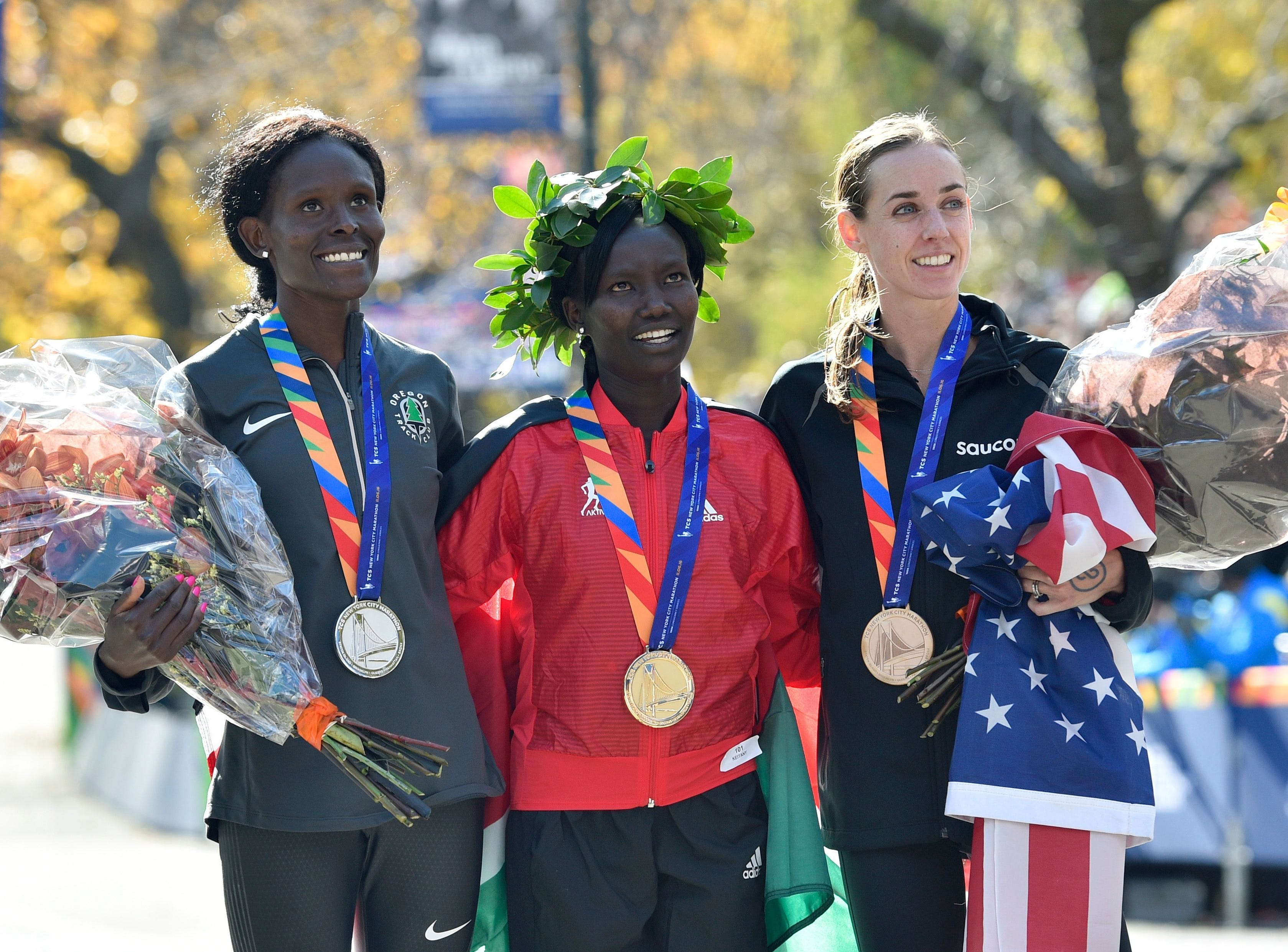 Second-place finisher Sally Kipyego (left), first-place finisher Mary Keitany (middle) and third-place finisher Molly Huddle (right) pose for a photo after the 2016 New York City Marathon. Huddle is a native of Elmira, NY.
