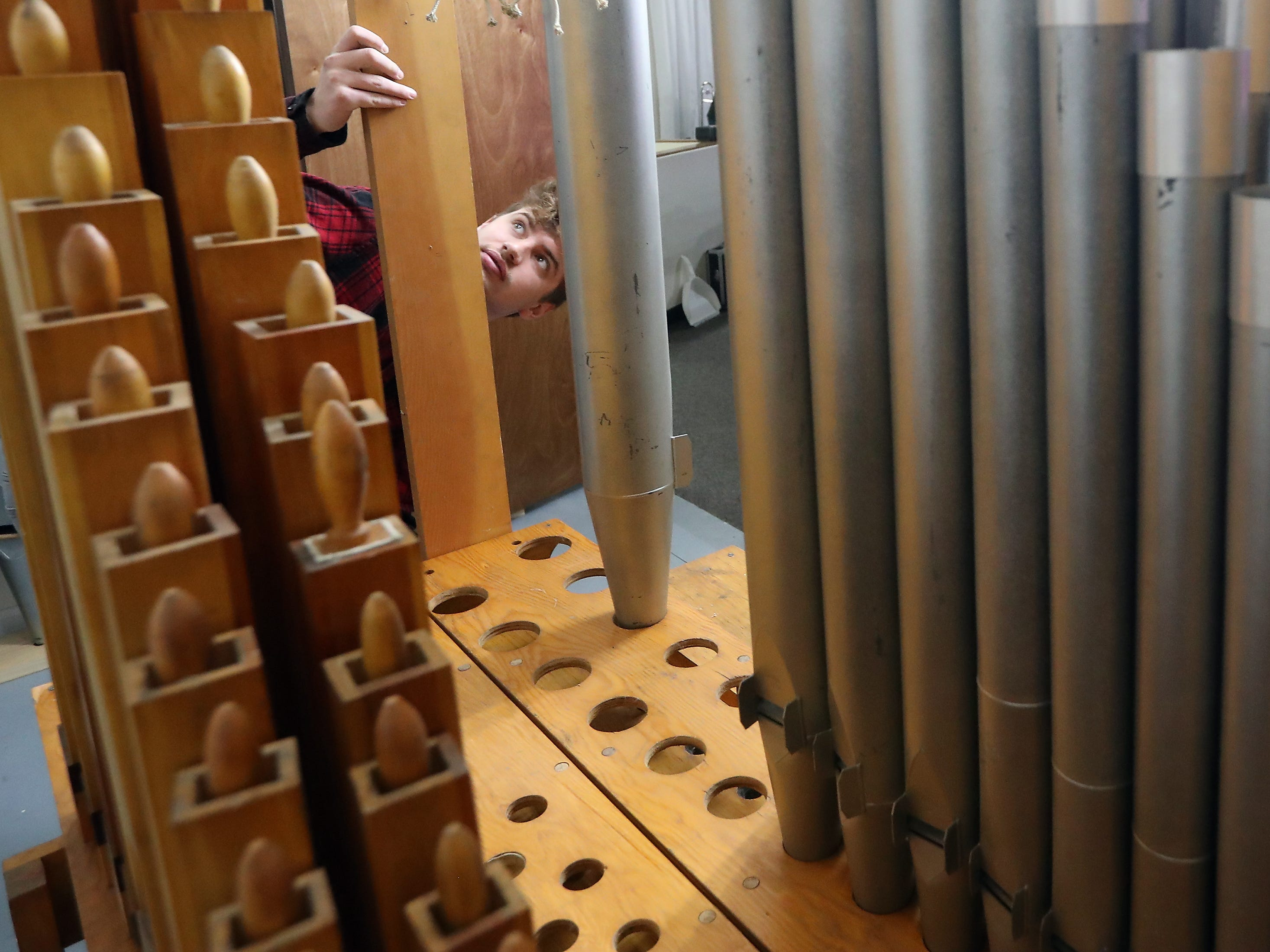 Bond Organ Builders of Portland apprentice Richard Uskovits attaches a brace piece that will hold the bigger pipes in place at Peace Lutheran Church in Bremerton on Tuesday, January 22, 2019.